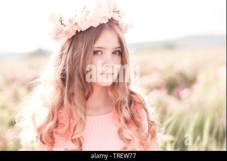 Lächelnde blonde Mädchen 14-16 Jahre alten posiert mit Rosen Kranz im Freien. Mit Blick auf die Kamera. - Stockfoto