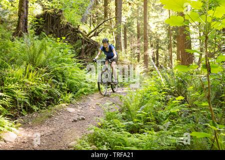 Glücklich lächelnde Frau Spaß reiten Mountainbike Radfahren auf einem Trail. Frauen Outdoor Adventure Sports. - Stockfoto