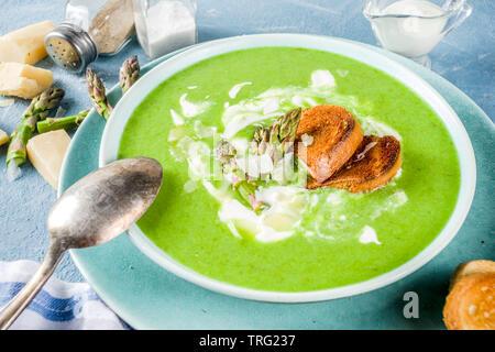 Gesunde hausgemachte Spargel Gemüse creme Suppe in einer Schüssel auf hellblau Schiefer, Stein oder Beton Hintergrund. Kopieren Sie Platz. - Stockfoto