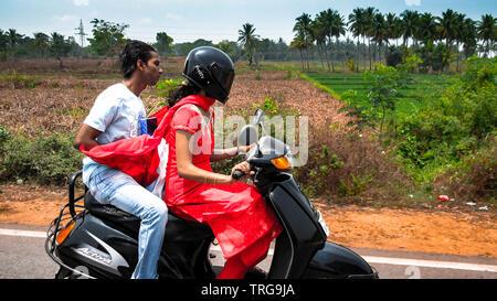 Junges hübsches Paar fahrten ein Motorrad in Indien, das Mädchen fahren ist und der Junge ist hinter einem Geschenk Paket sitzend, Indien. - Stockfoto