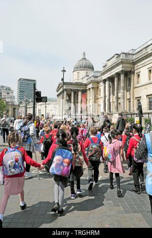 Gruppe der Grundschüler Schüler und Lehrer zu Fuß entlang der Straße der National Gallery London England UK KATHY DEWITT besuchen