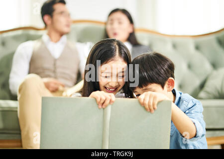 Zwei asiatische Kinder Bruder und Schwester auf dem Teppich lesen Buch sitzen zusammen in der Familie Wohnzimmer mit Eltern sitzen auf der Couch im Hintergrund.