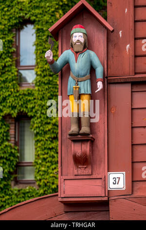 Wooden Abbildung eines Mannes mit roter Zipfelmütze auf der Wand eines historischen Holzhaus im Hanseatischen Viertel Bryggen, Torget, der Deutschen Wh - Stockfoto