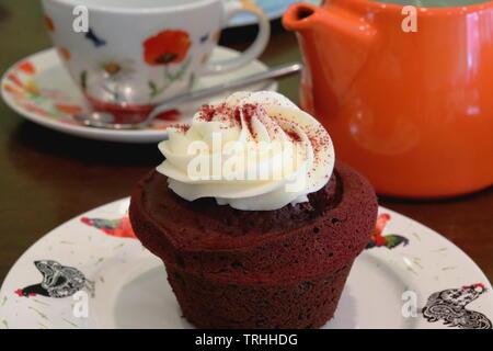Red Velvet Cake auf einer Platte in ein Cafe setzen mit Teekanne und Tasse, bereit zu essen - Stockfoto
