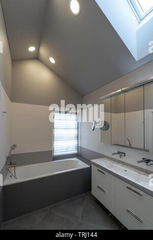 Bad im Dachgeschoss. Badewanne, Schrank mit Spülbecken und zwei Wasserhähne, Spiegel, Fenster und des Schiebedachs. - Stockfoto