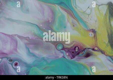 Nahaufnahme einer Acryl gießen Malerei in Teal, Magenta, Gelb, Violett und Weiß, das ähnelt der Aurora Borealis. - Stockfoto