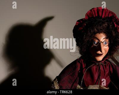 Marionette einer Hexe werfen Schatten an der Wand. - Stockfoto