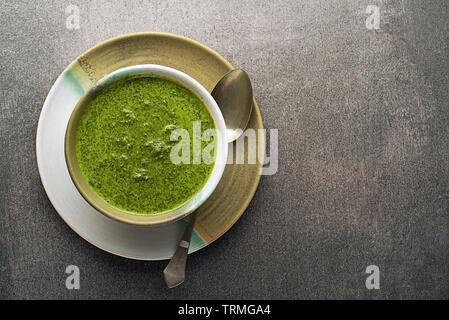 Frühling gesundes Essen. Grüne cremige Suppe mit Gemüse und Kräutern auf grauem Hintergrund - Stockfoto