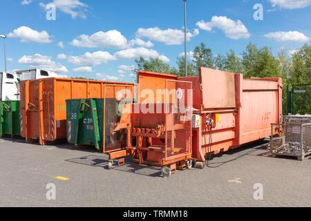 Orange abfallpressen stehen auf einem Fabrikgelände mit anderen Abfallbehälter neben Ihnen - Stockfoto