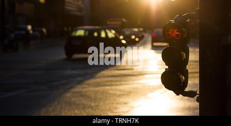 Rotes Fahrrad Ampel mit Autos, Verkehr im Hintergrund, während Sie im Sunrise - Stockfoto