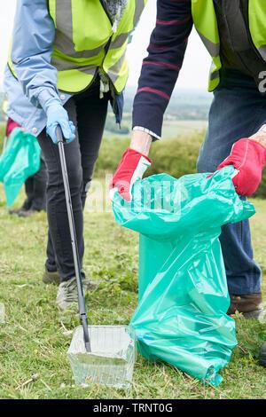 Nahaufnahme von Hilfsbereit Senior Paar sammeln Müll in der Landschaft - Stockfoto