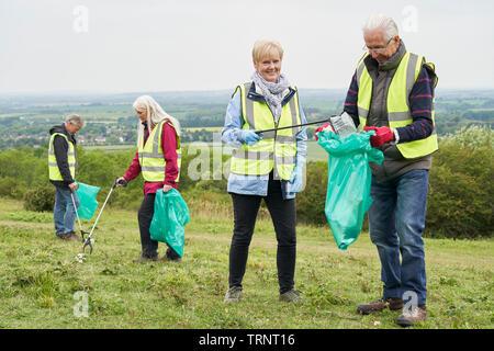 Gruppe hilfreiche Senioren sammeln Müll in der Landschaft - Stockfoto