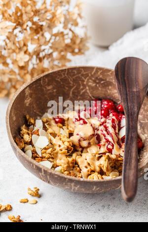 Hausgemachtes Müsli mit Preiselbeeren und Peanut Butter in einer Kokosnuss Schale. Gesunde vegane Ernährung Konzept. - Stockfoto