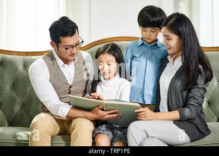 Asiatische Eltern und zwei Kinder zusammen auf der Couch lesen Buch zu Hause sitzen - Stockfoto