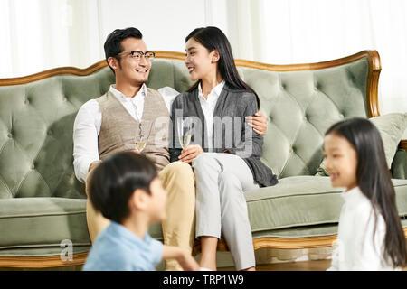 Asiatische Bruder und Schwester saß auf dem Teppich spielen, während die Eltern im Hintergrund für Chats, auf die Eltern konzentrieren. - Stockfoto