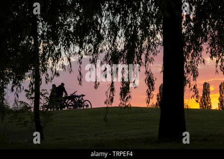 Abends britische Landschaft bei Sonnenuntergang. Zwei Radfahrer in Silhouette plaudern von picknickbank unter einem Silhouettiert Weeping Willow Tree im Freien in Country Park. - Stockfoto