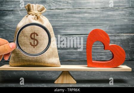 Beutel mit Geld und roten Herzen aus Holz auf der Waage. Geld gegen Liebe Konzept. Leidenschaft im Vergleich zu profitieren. Familie oder Karriere. Familie Psychologie. Geist - Stockfoto