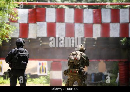 Bukarest, Rumänien - 10. Juni 2019: eine rumänische SIAS (äquivalent zu SWAT in den USA), Polizist und ein Special forces Soldat Zug zusammen in einem sho - Stockfoto