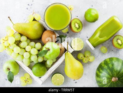 Glas und Flasche frischen Smoothie mit organischen Grün getönt Früchte in Weiß vintage Box auf Stein Küchentisch Hintergrund. Birne und Trauben mit Kiwi ein - Stockfoto