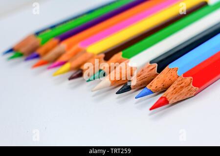 Nahaufnahme einer Auswahl von Multi Buntstifte Buntstifte, halten zusammen in eine Zeile Zeile Balken auf weißem Hintergrund angeordnet, flach. Selektive foc - Stockfoto
