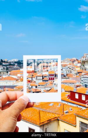 Nahaufnahme eines jungen kaukasischen Mann mit einem weißen Rahmen in seiner Hand die Gestaltung der Dächer der Altstadt von Porto, in Portugal, für die Simulation eines Instant p - Stockfoto