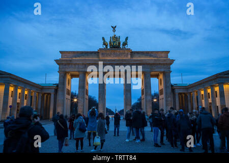 Viele Touristen fotografieren und an der berühmten und beleuchteten neoklassischen Brandenburg Gate (Brandenburger Tor) in Berlin, Deutschland in der Dämmerung - Stockfoto