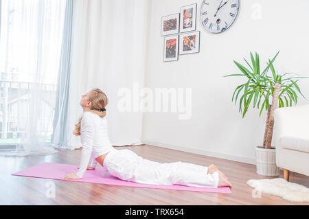 Yoga Zeit. Junge Frau ist Yoga zu Hause auf Yoga Matte, Cobra, Bhujangasana darstellen - Stockfoto