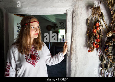 Portrait von schönen Mädchen in weißen ethnischen Shirt im traditionellen Haus im Dorf. Nationale Architektur Museum in Pirogowo, Kiew, Ukraine - Stockfoto