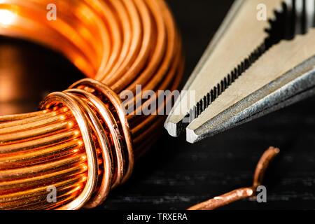 Makro Bild einer Spule aus Kupferdraht und einer Spitzzange. Arbeiten Werkzeuge und Materialien der Elektriker für den Job gemeinsam Empfohlene - Stockfoto
