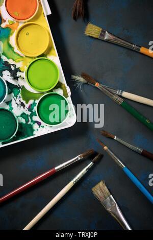Box mit Wasserfarben und Pinsel auf einem Tisch. Stockfoto