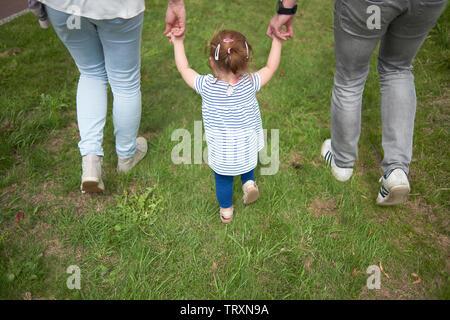 Ehepaar Hand in Hand mit ihrem ersten Kind geboren, ihr zu helfen in Balance zu halten, wenn sie laufen lernen - Stockfoto