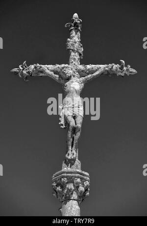 Schwarzweiß-Bild von einem Stein Statue von Christus am Kreuz auf einem Friedhof in La Feuillée, Bretagne, Frankreich.