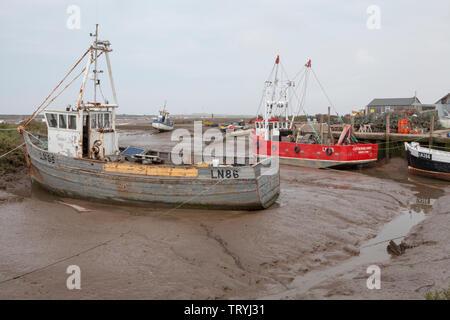 Hölzerne Fischerboote bei Ebbe an brancaster Staithe Quay, im Dorf Brancaster Staithe auf die Küste von Norfolk in England - Stockfoto