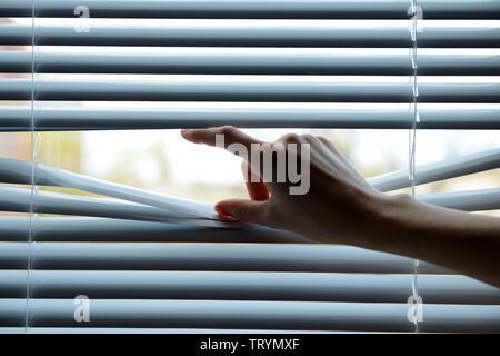 Weibliche Hand trennen Lamellen von Jalousien mit einem Finger durch zu sehen - Stockfoto