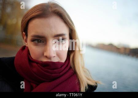Porträt einer schönen jungen Frau trägt einen roten Schal im kalten Tag warm zu halten. - Stockfoto