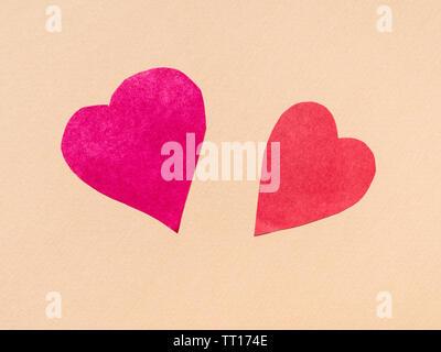 Zwei Herzen von rot auf beige Papier Hintergrund ausschneiden - Stockfoto
