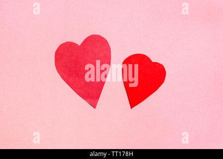 Zwei Herzen aus rotem Papier schneiden auf rosa Papier Hintergrund - Stockfoto