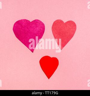 Drei verschiedene Herz aus roten Papieren auf rosa Papier Hintergrund ausschneiden - Stockfoto
