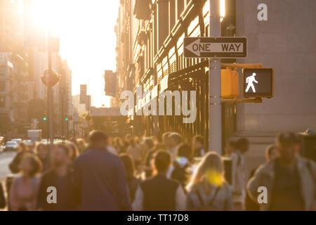 Sonnenlicht scheint auf den geschäftigen Menschenmassen von anonymen Personen auf der Straße in Manhattan, New York City NYC - Stockfoto