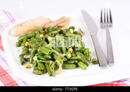 Salat mit grünen Bohnen und Mais auf Platte, isoliert auf weißem - Stockfoto
