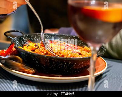 Essen valencianische Paella in einem schwarzen Pfanne mit einer Gabel. Typische spanische Küche. Meeresfrüchte und Tourismus - Stockfoto
