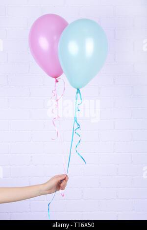 Hand mit Blau und Rosa Ballons auf Ziegel Wand Hintergrund - Stockfoto