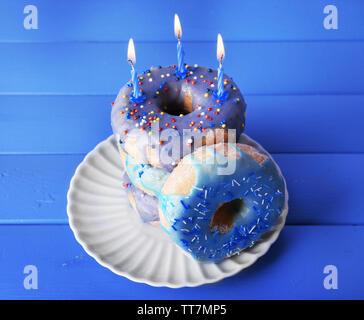 Köstliche Krapfen mit Puderzucker und Geburtstag Kerzen auf hölzernen Hintergrund - Stockfoto