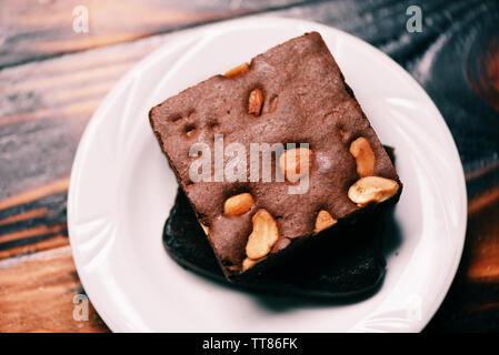 Brownies Kuchen auf dem Tisch/Chocolate Cake Slice mit der Mutter in der Platte auf hölzernen Hintergrund - Stockfoto