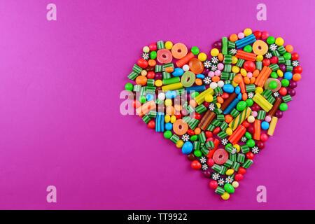 Bunte Bonbons in Herzform auf lila Hintergrund - Stockfoto