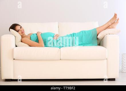 Schwangere Frau liegt auf einem Sofa im Zimmer - Stockfoto