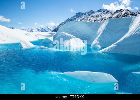 Der Gipfel des Mt Wickersham über den Matauska Gletscher in Alaska droht. Ein Crystal Blue Pool sitzt unter dem Gipfel mit Flossen der weißen Eis heraus o - Stockfoto