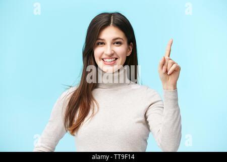 Schönen jungen kaukasischen Frau, eine Nummer Eins, in die Kamera lächeln suchen, auf blauem Hintergrund isoliert - Stockfoto