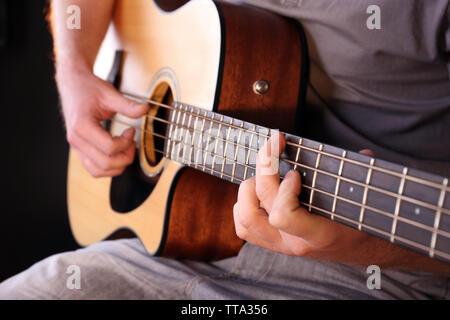 Junge Mann spielt auf der Akustikgitarre Nahaufnahme - Stockfoto
