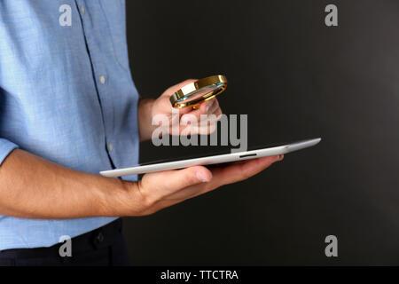 Geschäftsmann mit Lupe und digitale Tablette auf dunkelgrauem Hintergrund, suchen und prüfen Konzept - Stockfoto